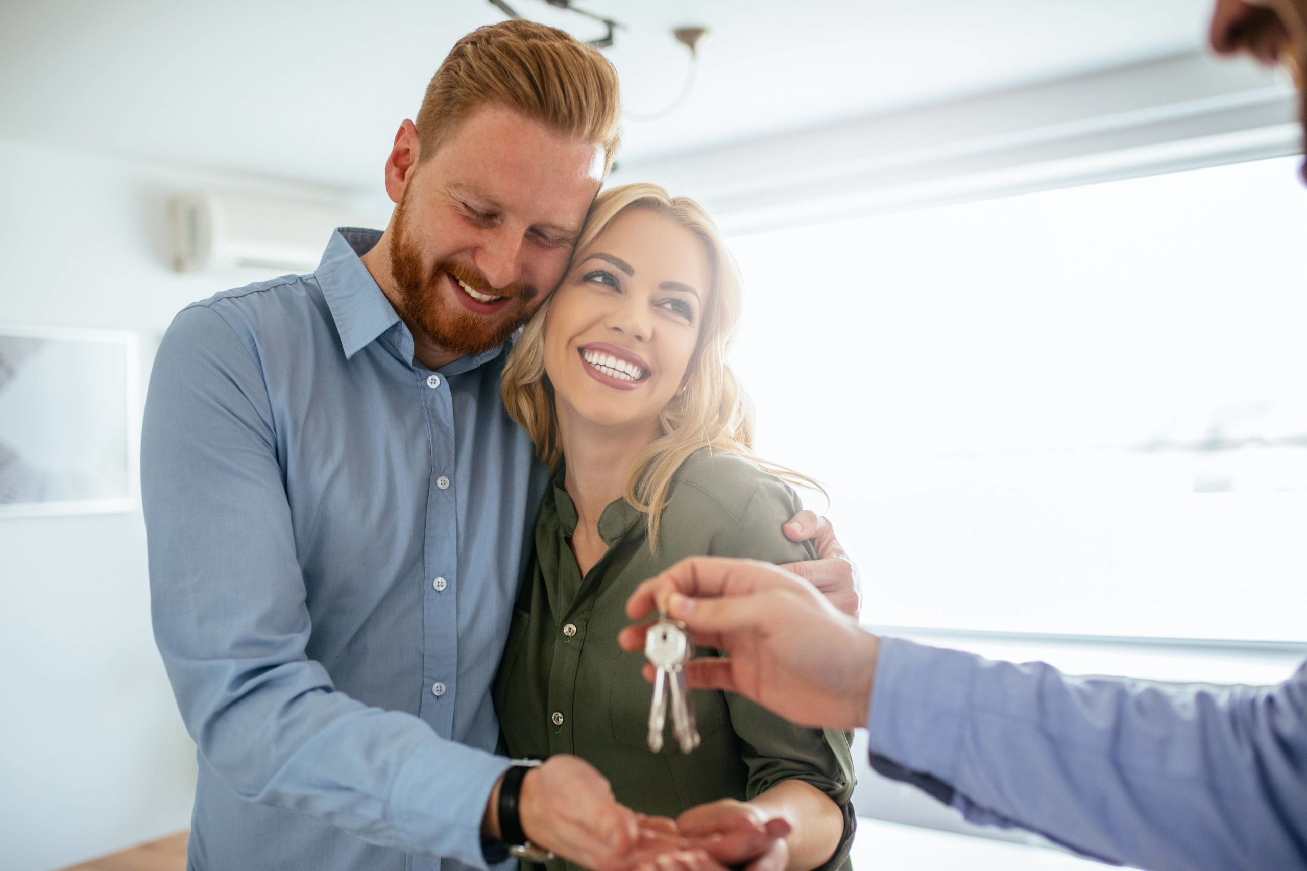 Couple with their arms around each other accepting the keys to their new home together.