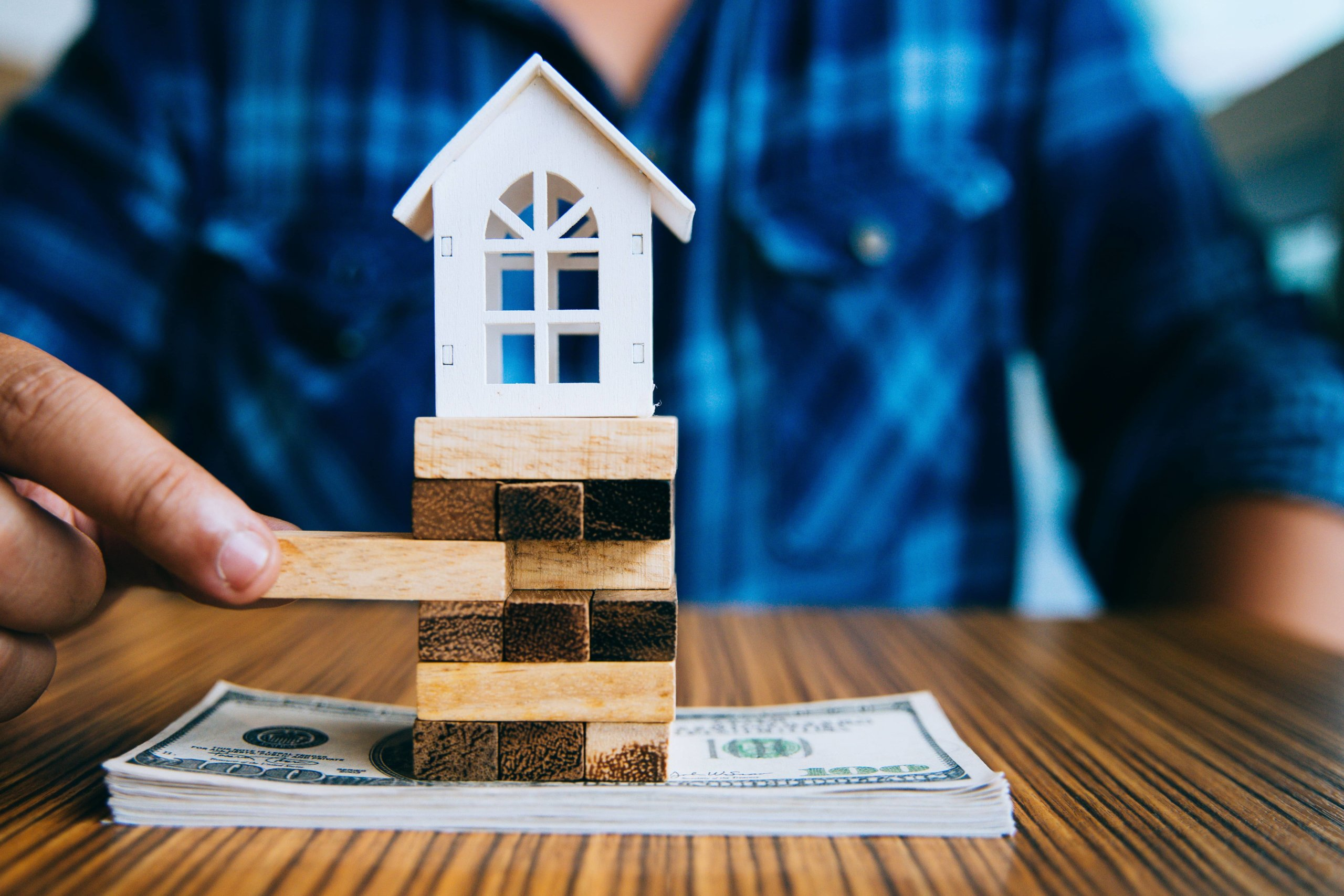 Man in blue shirt playing jenga sandwiched between a house and a stack of money.