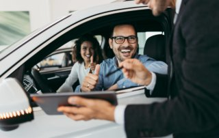 Middle aged couple sitting in their new car giving the car salesman a thumbs up.