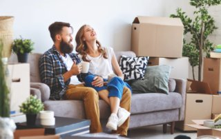 Your couple sitting on the couch in their new home surrounded by boxes that need to be unpacked.